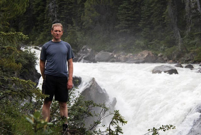 """John standing beside the wild Yoho River"""