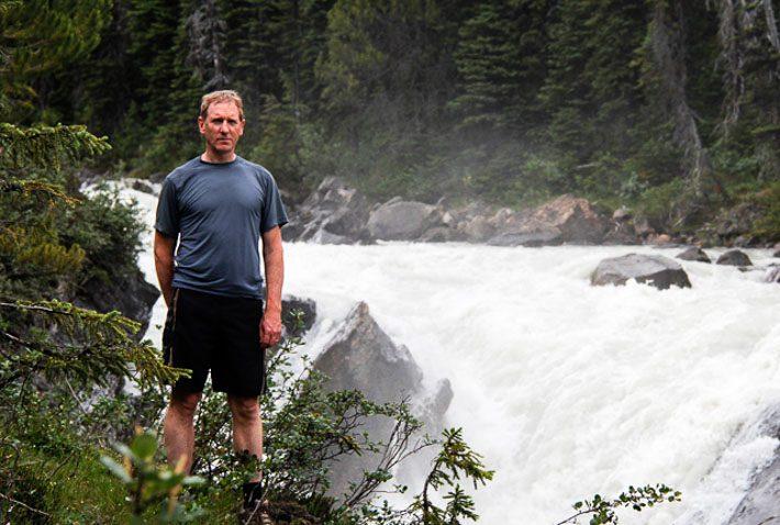 John standing beside the wild Yoho River
