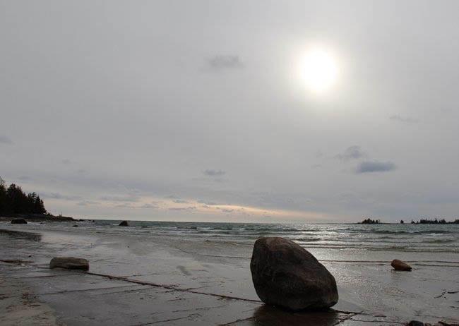"""Lone boulder by the water under November skies"""