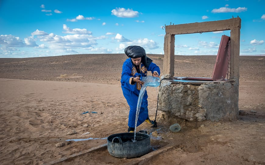 Man filling the drinking pot for any camels that might happen by